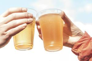 Two plastic glasses with beer in female hands on a sky background