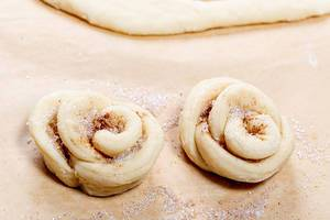 Two raw buns with cinnamon and sugar in the shape of flowers