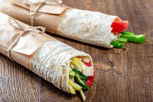 Two ready-made Shawarma on a brown wooden background