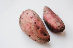 Two red potatoes on white background.