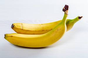 Two ripe bananas on a white wooden table (Flip 2019)