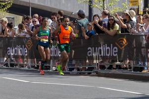 Two runners running side by side and holding green rope - London Marathon 2018