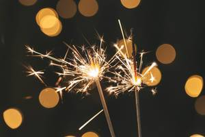 Two sparklers are lit on a blurred background of a glowing garland (Flip 2019)