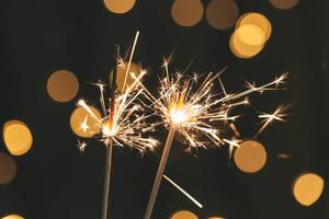 Two sparklers are lit on a blurred background of a glowing garland