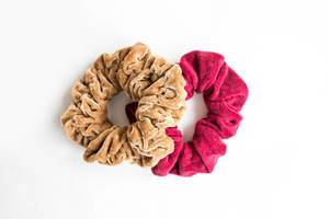 Two velvet scrunchies on white background top view