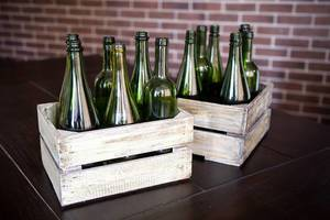 Two wooden boxes of different shaped green wine bottles on rustic background