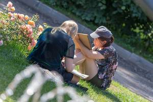 Two young women sitting on grass and painting in Gorky Park