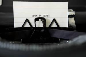 Type it HERE: auf einem Papier in einer Vintage Schreibmaschine aus dem Blickwinkel des Schreibers
