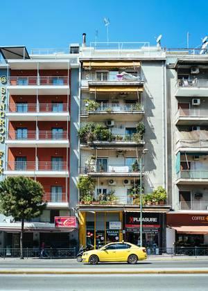 Typisches griechisches Wohnhaus mit grünen Balkonen und gelben Taxi vor der Tür, in Athen (Griechenland)