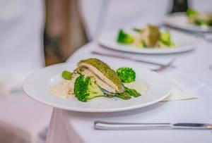 Überbackenes Fischfilet auf Brokkoli und grünem Spargel mit Soße auf weißem Teller