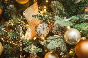 Uhren Dekoration am Weihnachtsbaum mit einer goldenen Socke und Kugeln