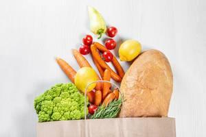 Umweltfreundliche Einkaufstasche aus Papier, gefüllt mit gesundem Obst und Gemüse