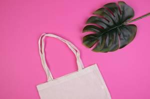 Umweltfreundliche, wiederverwendbare Einkaufstasche aus Baumwolle neben Blatt vor pink