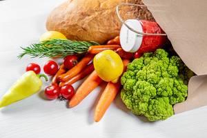 Umweltschonende Papiertüte mit einem vegetarischen Einkauf gefüllt, wie Brot, Brokkoli, Karotten, Tomaten und Gewürzen