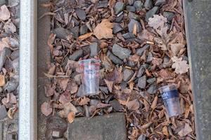 Umweltverschmutzung - Plastikbecher und Zigarettenstummel liegen neben Schiene