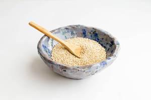 Ungekochte Quinoa Samen mit einem Holzlöffel in einer blauen Tonschüssel auf weißem Hintergrund