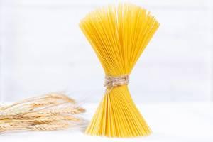 Ungekochte Spaghetti zu Bund geschnürt neben Weizen