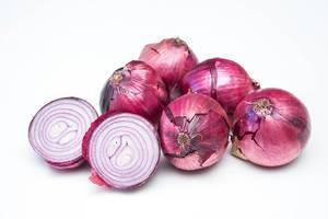 Ungeschälte und halbierte rote Zwiebel, im Hintergrund weitere Zwiebeln mit Schärfentiefe