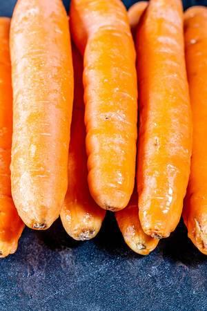 Ungeschälte und rohe Karotten für gesunde Ernährung mit Carotin auf dunklem Hintergrund