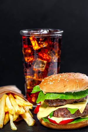 Unhealthy food concept-hamburger, Cola with ice cubes and fried artofel on black background (Flip 2019)
