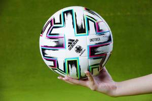 Uniforia official EURO 2020 ball in hands of a woman, green background