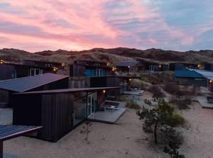 Untergehende Sonne spiegelt sich in den Dächern von Ferienhäusern in den Niederlanden