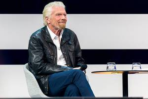 Unternehmer Richard Branson sitzt bequem und spricht auf der Digital X in Köln