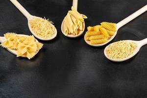 Unterschiedliche Formen von Pasta in Holzlöffeln auf schwarzem Hintergrund