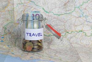 Vacation money savings in a glass jar on world map