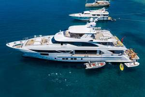 Vacation on a luxury motor super yacht with outdoor area, sundeck and dinghies at the greek coast of Artemios, Paros