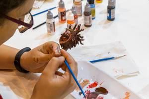 Vallejo Acrylfarben: Eine Frau bemalt eine Spielfigur Auf der Spiel in Essen
