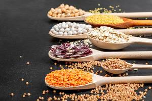 Various cereals and legumes in wooden spoons