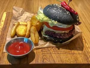 Veg Kuro Burger beim Avocado Cafe: Frikadelle aus Linsen und Müsli, mit Holzkohle geschwärztes Brötchen, Erdnusssauce, Tomate, Essiggurke, Kopfsalat, Chili