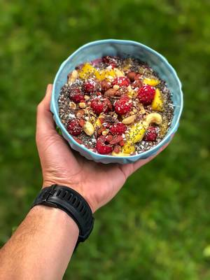 Vegan Acai Bowl with mango, nuts, raspberries, goji berries, chia and chocolate