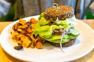 Vegan and gluten-free food in Chicago: Inside Out Quinoa Burger by True Food Kitchen with hummus, tzatziki, organic tomato, butter lettuce, cucumber, red onion, avocado, feta