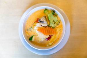 "Vegan appetizer ""Tom Yum"", is a coconut milk based soup, spicy aromatic, with tofu, fresh carrots, broccoli and mushrooms"