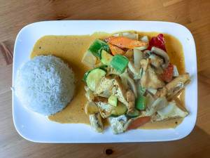 Vegan Asia Meal - Red thai curry with tofu, zucchini, mushrooms, bellpepper, carrots and rice on a plate on wooden table