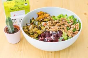 Vegan Bowl mit gegrilltem Gemüse, rote Beete, Edamame, Walnüsse, Salat, Reis und Soja-Sesam Dressing in weißer Schale