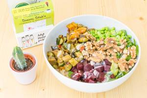 Vegan Bowl with grilled vegetables, beetroot, edamame, walnuts, lettuce, rice and soy-sesame dressing in white bowl