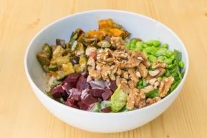 Vegan Bowl with grilled vegetables, rice, walnuts and edamame in a white bowl on a wooden table