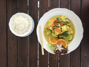Vegan food with vegetables like broccoli, zucchini, sweet pepper and cauliflower with tofu in a meatless curry turmeric sauce, next to chopsticks & rice bowl