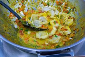 Vegan organic pasta cappelletti with pumpkin-apple filling are prepared in a sauce with carrots and peppers