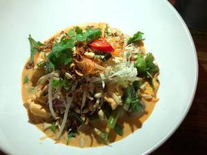 Vegan organic tofu in red coconut curry with beans, carrots, chestnuts, onions, mushrooms, shiitake mushrooms on fragrant rice, served with fresh soy sprouts, exotic herbs, peanuts and fried onions