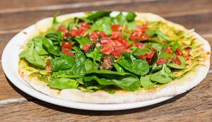 Vegan Pizza with green Pesto, Tomato and Spinach