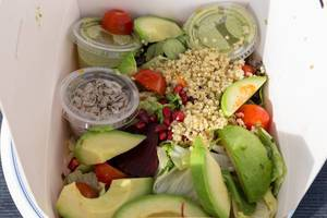 Vegan quinoa salad with avocado, tomato, beetroot, guacamole and seeds in a take-away paperbox