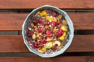 Vegane Acai-Bowl mit Mango, Nüssen, Himbeeren, Gojibeeren, Chia und Schokolade