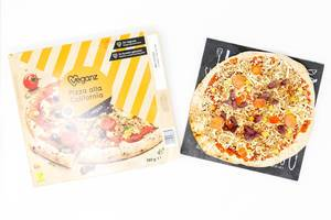 Vegane Backofenpizza auf Pizza-Steinplatte neben Pizzakarton