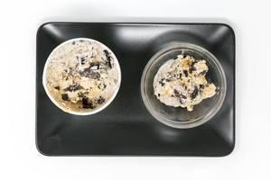 Vegane Ben and Jerrys Eiscreme ohne Milch mit Erdnussbutter und Keks Geschmack in einem Schälchen und Verpackung auf einem schwarzen Teller in der Aufsicht