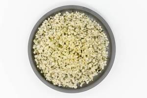 Vegane Bio-Hanfsamen, geschält auf einem schwarzen Teller in der Aufsicht