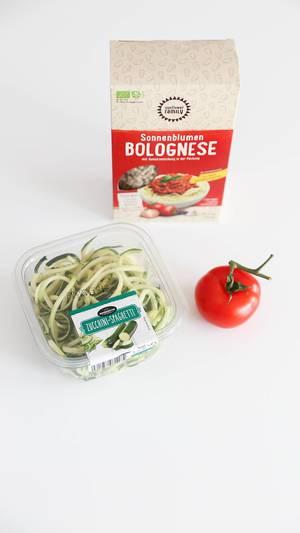 Vegane Bolognese aus Sonnenblumenkernen mit Gewürzmischung, neben einer Tomate und Zucchini-Spaghetti, vor weißem Hintergrund